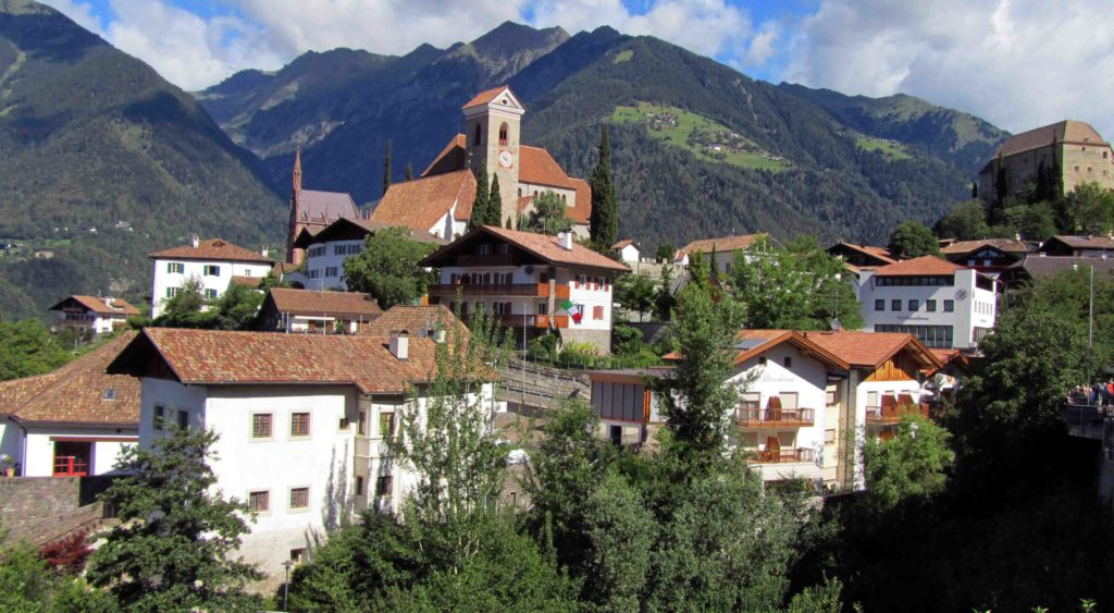 This is Schenna a village in South Tyrol where you can see the castle and the chruch of Schenna. This landscape is characterised by breath-taking mountains and warm valleys, lined with forests, wine and apple farms. Crystal clear rivers and lakes, impressive castles and alpine farmhouses on top of the mountains.